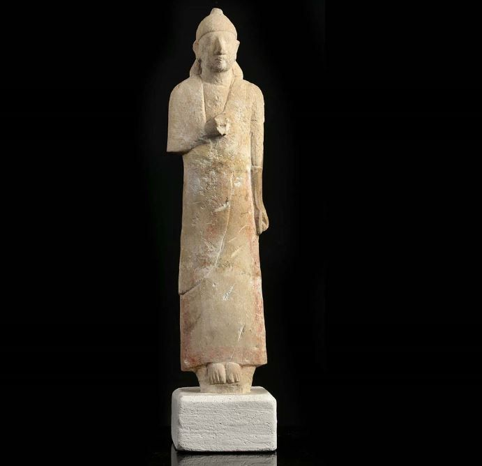 Cypriot Limestone figure of a male worshipper, Cypro-Archaic period, 6th century B.C. Depicted standing with his feet together, the right arm bent, holding the long tunic with the hand, the long hair pulled behind the ears, covered by a pointed bonnet or helmet, with remains of red pigment along the edges of the robe, 33 cm high. Private collection