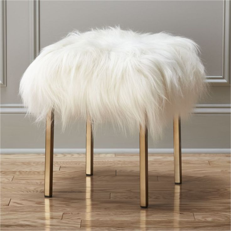 shear fun.  Playful pile of authentic Icelandic sheepskin cozies up as statement stool for the living room, bedroom or study.  Generously sized larger than others we've seen, extra-soft shearling juxtaposes sleek rectangular gold metal legs. 100% sheepskin woolSheet metal legs with gold finishEach shearling is unique and follows strict directives for environmental preservation and protection. Made in Taiwan.