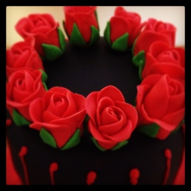 Flowers on top of gothic cake.
