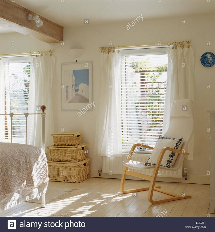 Download this stock image: Scandinavian style wooden chair and wicker chests in white bedroom with Venetian blinds and white voile curtains on window - EJDJ51 from Alamy's library of millions of high resolution stock photos, illustrations and vectors.