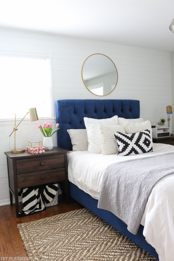 Love this calming bedroom space with the navy headboard and gold accessories. The inexpensive mirror above the bed looks classy and on-trend.