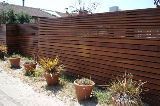 Great modern privacy fence made out of ipe, a sustainably harvested Brazilian hardwood, in two thicknesses, we think it's the fact that boards are laid horizontally that makes it so uniquely gorgeous. (pinned from Apartment Therapy web site.)