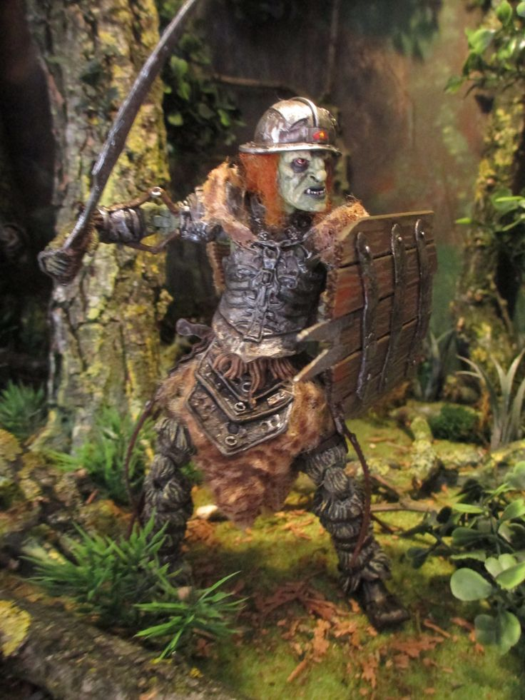 Custum from the body of Gorbag, the Overseers head. Clothing and weapons are handmade.  The helmet is a custom of a playmobil helmet. The figure is standing in my display box of Treebeard (Fangorn forest)