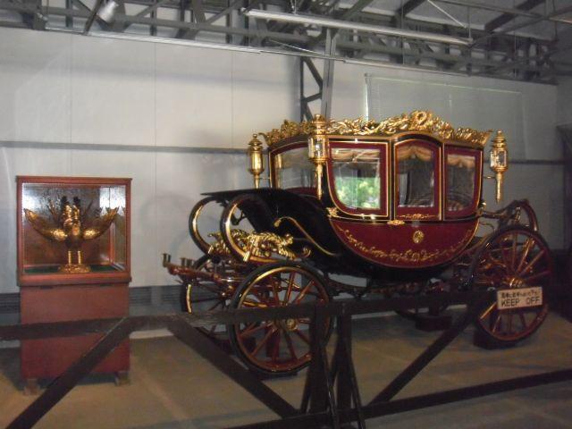 儀装馬車1号。昭和三年製、溜塗の外装に、鳳凰を頂いた外観は別格です。横のケースに入った鳳凰が上に載ります。