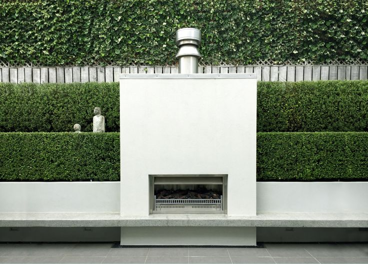 Wellington courtyard with Outdoor fire with layered hedging, cantilevered concrete hearth.