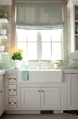 white cabinets, white/gray counters, soft colored green backsplash, farmhouse sink, color with towel and roman shade