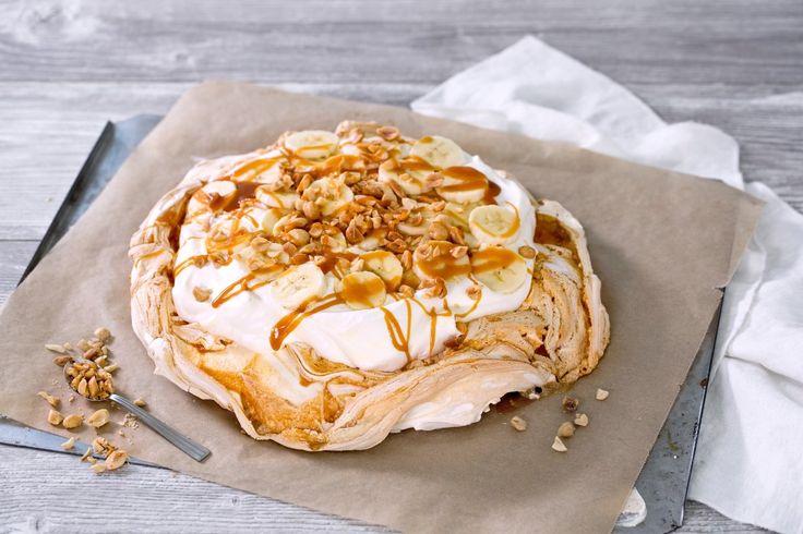 Dette er pavlovaen for karamell-elskere! Her er selve bunnen marmorert med karamellsaus og kaken er toppet med vaniljekrem, banan, salte peanøtter og mer karamell