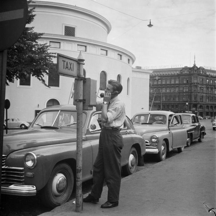 Vuonna 1957 taksinkuljettajan virka-asusta oli lupa helteellä riisua takki ja lakki. Taksinkuljettaja Ruotsalaisen teatterin tolpalla. Helsinki 17.8.1957.  Valokuvaaja Eero Markkula/Suomen valokuvataiteen museo/Alma Media/Uuden Suomen kokoelma