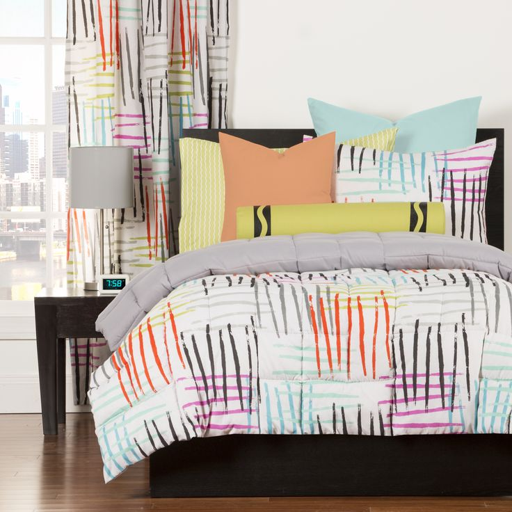 Modern brush strokes and crosshatches create an illusion of shade and texture to brighten and embellish your space. A colorful design sits atop a white background. This stunning comforter set reverses to solid grey.
