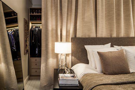 garderobe derrière un rideau derrière le lit