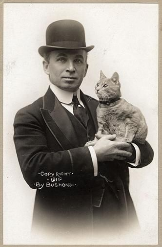 """The first cat to cross the Atlantic by air was the diminutive Kiddo, shown here with Melvin Vaniman, chief engineer of the airship America in 1910. The America was the first aircraft to carry radio equipment, and Vaniman ordered a wireless message sent to [owner Walter] Wellman's secretary back on shore—so the historic first radio communication from an aircraft in flight reads: """"Roy, come and get this goddamn cat."""""""