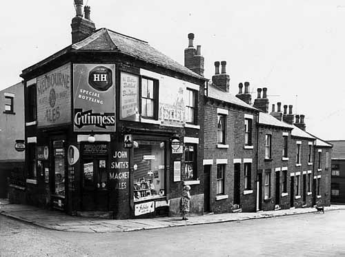 On 1 September 1965, this photograph was taken prior to the great Leeds slum clearance of the 60s and 70s. The view looks along Speedwell Street from Melville Road. The numbers run to the right in descending order from number 38 on the left which is an off licence run by Marie T McCullough. Advertisements for Melbourne Ales, Guinness and John Smiths Magnet Ales can be seen.