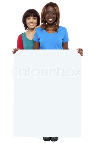 Image of 'Casual girls standing behind blank whiteboard' on Colourbox