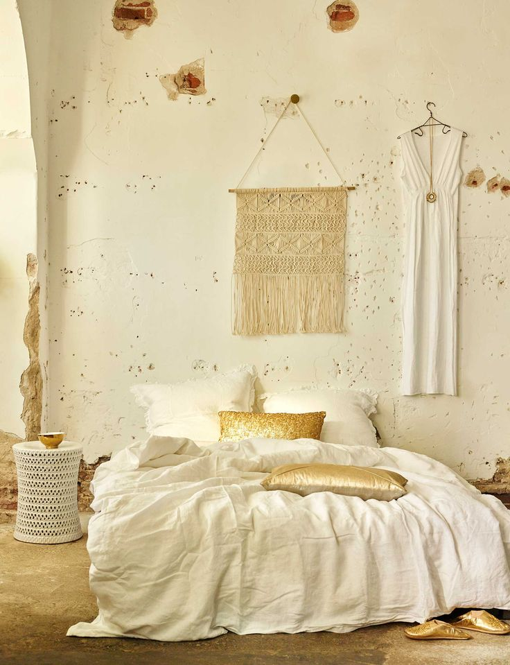 Creamy white bedroom with raw walls and golden details