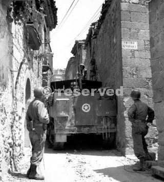 HALF-TRACK DETOURING THROUGH A SIDE STREET When the enemy retreated through the Sicilian villages