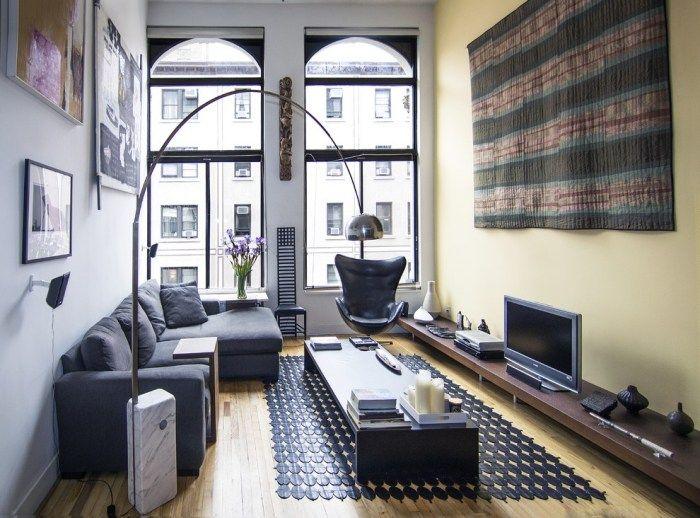 eine pastellgelbe und eine hellgraue Wand im schmalen Wohnzimmer
