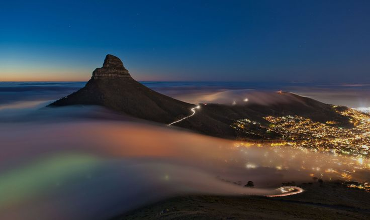 Low clouds appear to take on all the colors of the rainbow as it passes Lion's Head into Cape Town's City Bowl.