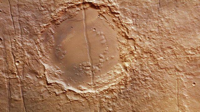 L'agenzia spaziale tedesca DLR ha pubblicato fotografie di un curioso cratere solcato da una profonda frattura che lo divide in due nell'area di Marte chiamata Memnonia Fossae. Si tratta di foto scattate dalla macchina fotografica High Resolution Stereo Camera (HRSC), uno degli strumenti della sonda spaziale Mars Express dell'ESA. Leggi i dettagli nell'articolo!