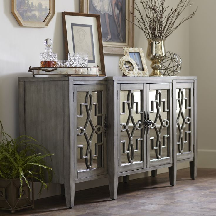 Birch Lane Hurley Mirrored Credenza - This mirrored four-door credenza features antique mirrored glass set behind intricate open scroll fretwork. Includes a fixed interior shelf, tapered legs, and a soft, hand-painted grey finish for a vintage look.