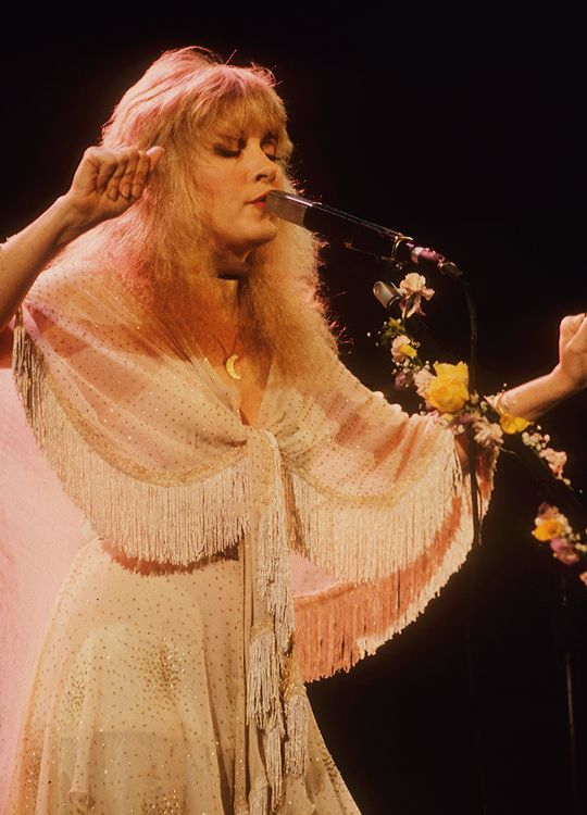 Stevie singing onstage wearing a dazzling cream dress and shawl and her gold half-moon pendant ~ ☆☆♥♡☆♥☆ ~ her microphone stand is decorated with matching roses and flowers; her nails are very short here and not painted with nail polish