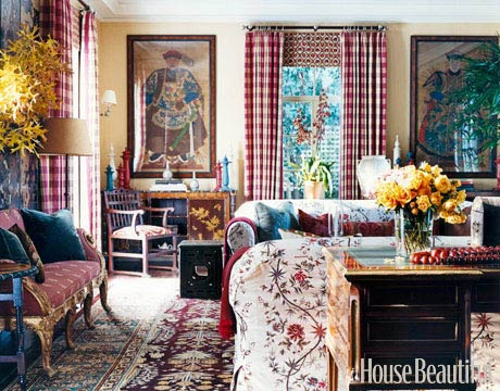 A Cozy Living Room Designed by Michael S. Smith, this living room features exotic Chinese ancestor portraits hung over a pair of chinoiserie cabinets, which could have looked very formal, but the cozy Eaton Check curtains in claret bring the room gently down to earth. Antique Italian loveseat covered in Lisbon Stripe in red. Both fabrics by the designer Cowtan & Tout. A pair of sofas is upholstered in Le Grand Genois Multicolore from Pierre Frey.