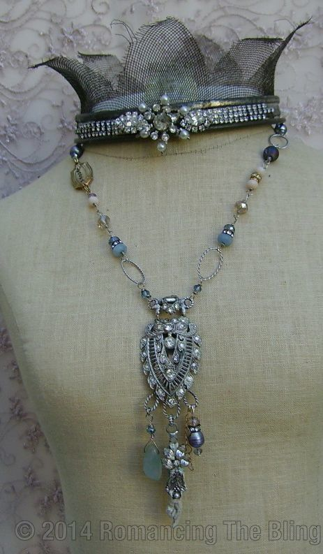 Great necklace with its odd beads and gems, and the rhinestone dress clasp or brooch.