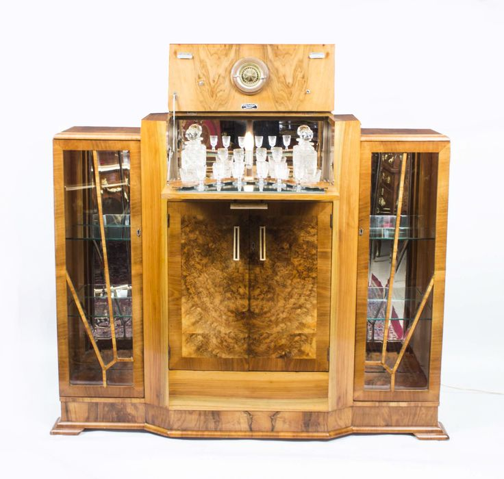 This is a fantastic antique Art Decoburrwalnutcocktail cabinet, circa 1920. The raised central section opens to reveal a mirrored and fitted interior to store your glasses and decanters. It is flanked with cupboards with glazed doors that have fan-shaped glazing bars typical of the Deco period and and glass shelves. The twin doors below open to reveal a cupboard for storing the bottles of drinks.The cabinet rests on a stepped cushion plinth and has its original chrome…