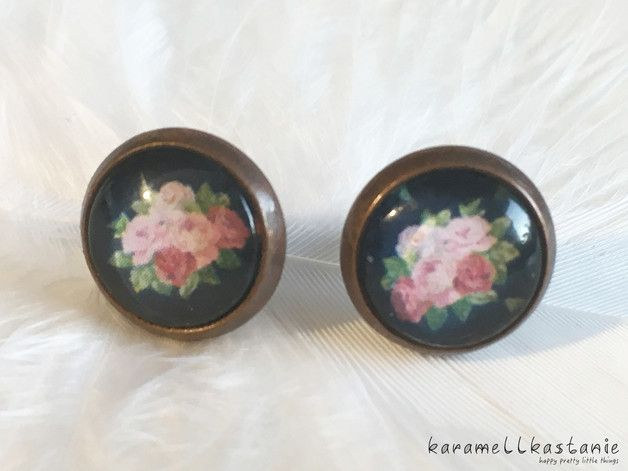 Diese wunderschönen Ohrstecker zeigen einen vollen Rosenstrauß auf dunkelblauem Hintergrund.  Durchmesser Cabochon inkl. Fassung: ca. 1,2 cm  Fassung: kupferfarben, antik  (Disclaimer:...