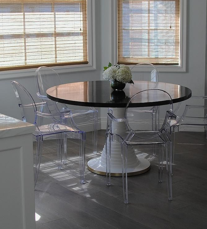 Breakfast room boasts a round black and white pedestal dining table placed on an engineered walnut floor surrounded by Ghost Chairs lit by natural light streaming in from windwos dressed in bamboo roman shades.