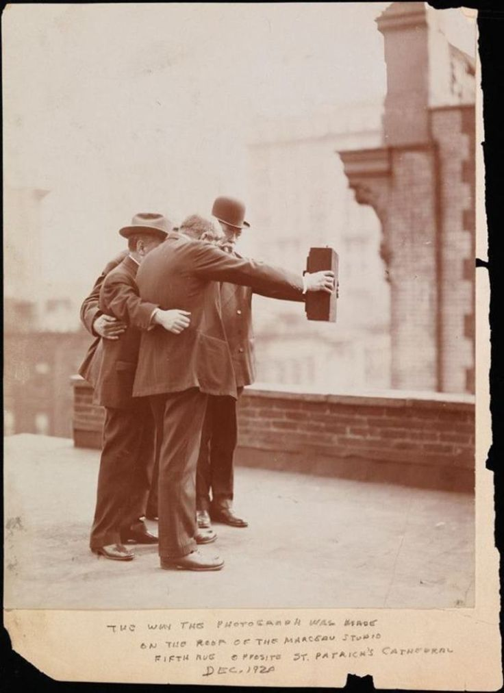 "1920: ""Selfie""                                                          Side view of photographers posing together for a photograph on the roof of Marceau's Studio, while Joseph Byron holds one side of the camera with his right hand and Ben Falk holds the other side with his left hand."
