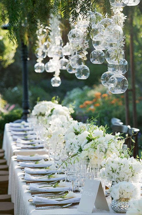Gorgeous glass bubbles hang over a long banquet table for a fresh, outdoor wedding celebration.