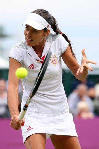 Ana Ivanovic Photos Photos - Ana Ivanovic of Serbia returns a shot to Kim Clijsters of Belgium on Day 5 of the London 2012 Olympic Games at Wimbledon on August 1, 2012 in London, England. - Olympics Day 5 - Tennis
