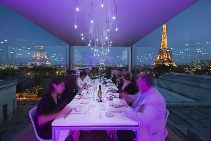 Dine Next To The Eiffel Tower At Paris' Nomiya...atop the roof of Paris' Palais de Tokyo contemporary art space is a tiny 12 person restaurant...shipping container-esque space. Designed in 2008 collaboration of Laurent & Pascal Grasso... One table above the Seine, chef Stassart & team make modern French meals. The Eiffel Tower is in sight line but there is a reflective panel that allows it to be seen as a conceptual experience too -- detail in furniture/finishes (note Eames molded chairs).