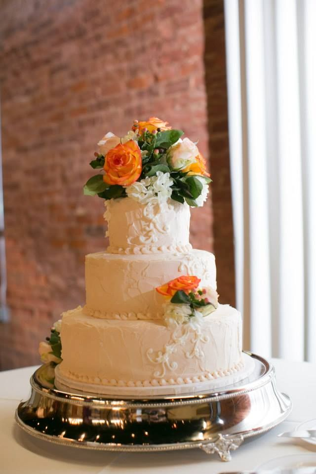 Maggie and David's cake is topped and decorated with with spray roses, coral roses, hydrangeas, and berries.: