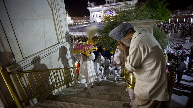 This gentleman is carrying the Guru Granth Sahib, holy book of Sikhism.