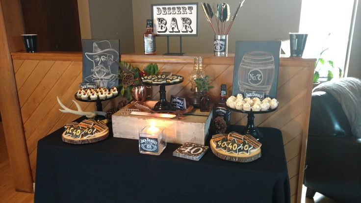 JD infused jack and coke mini cupcakes as well as JD Honey whiskey infused mini cupcakes, plus theme cookies done by Cuppycakes by Julie. Dessert bar décor by Pocket Full of Parties.