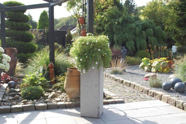 Pflanzkübel Betonoptik Grau im Garten hübsch bepflanzt. Weitere Pflanzkübel Beton finden Sie unter https://www.vivanno.de/pflanzkuebel/materialien/beton/