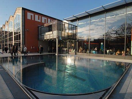 """Vom Inneren aus haben die Besucher einen herrlichen Blick auf die grüne Oase mit altem Baumbestand. Ein besonderer Genuss ist es, mit dieser Aussicht durch das 25-m-Becken zu schwimmen. Bei schönem Wetter öffnet sich die Schwimmhalle durch versenkbare Tore in der Glasfassade auf die Außenterrasse und die weitläufige Liegewiese – das Südbad wird damit zum """"Freibad mit Dach"""".  Im Innen- und Außenbereich schafft ein neues Beleuchtungskonzept eine angenehme, abwechslungsreiche Atmosphäre. Der…"""