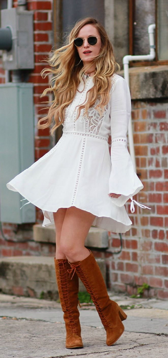 Fall boho outfit styled with bell sleeve white lace dress, suede lace up boots, and round Ray Ban sunglasses