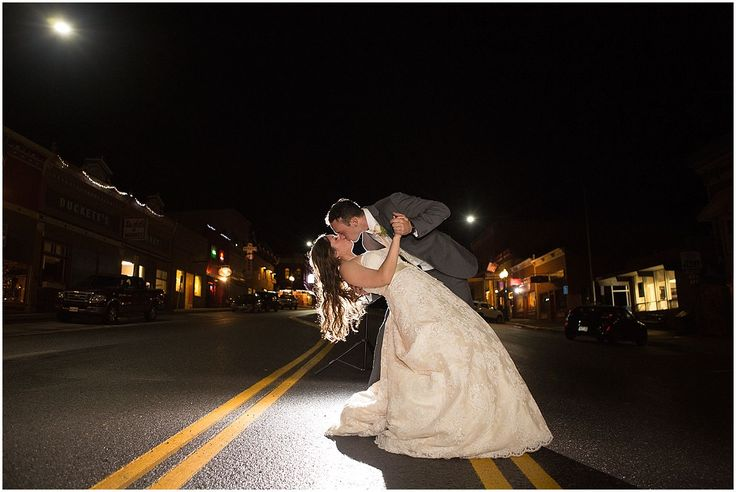 Outside of their Ouray Western Hotel wedding reception, the groom dips his bride for a night portrait on the street.