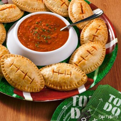 """Fantastic Football Party Food Ideas -Party CityWhen the stakes are high and the guests are hungry, try out this winning move! To make these football pizza pockets, cut out football shapes from homemade or packaged pastry dough and fill with your favorite ingredients, like mozzarella, pepperoni and pizza sauce. Slice some """"laces"""" into the top before baking and serve with a side of marinara for dipping. Touchdown!"""