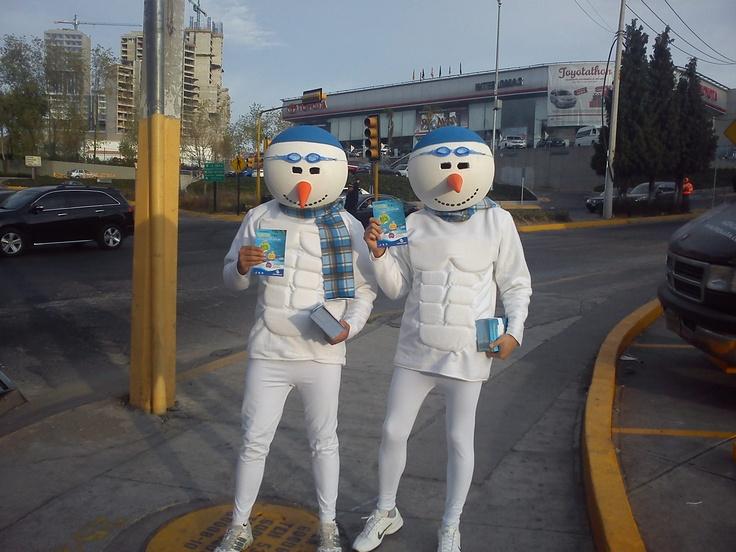 Atléticos muñecos de nieve repartiendo flyers para una promoción navideña de una cadena de Fitness.