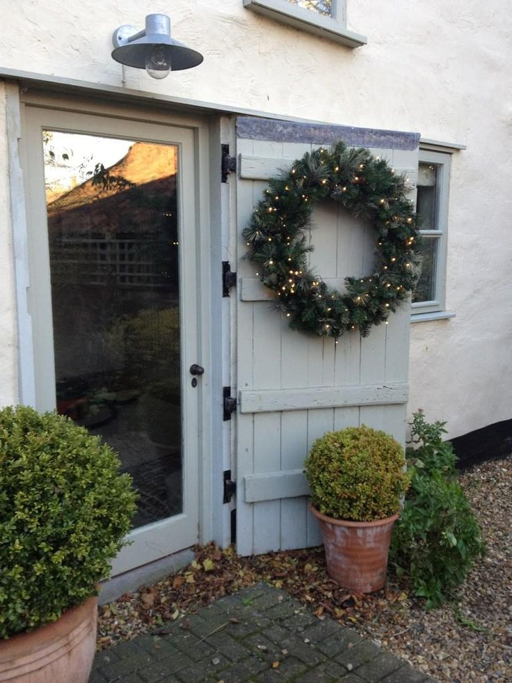 like this idea of using a character full door as a shutter and then a glazed door to let the light flood in, clever way of combining traditional rustic with crisp modernism.  A wreathed door painted in French Gray. Wall in Farrow & Ball's String Masonry paint