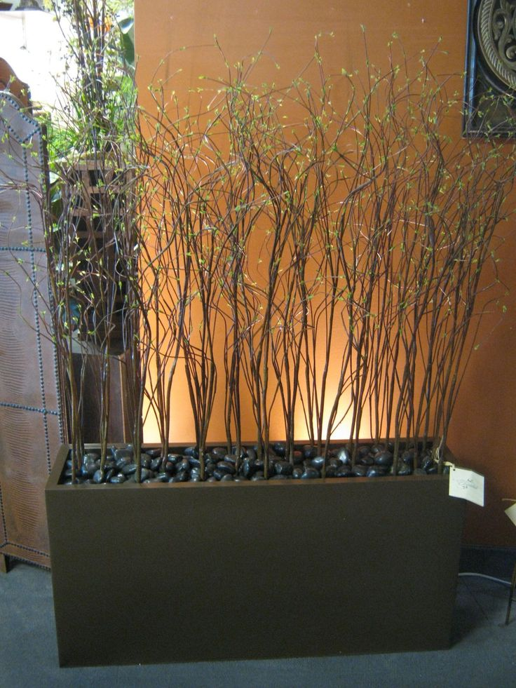 Willow branches and river rock in planter boxes for deck decor - I would add some lighting and a more interesting planter box.