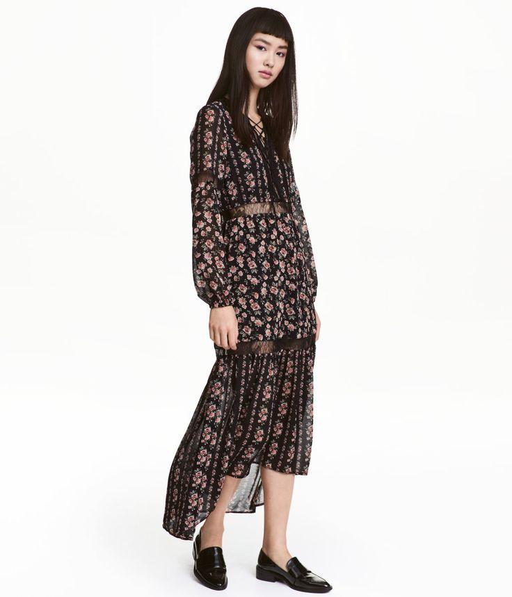 Sort/Roser. Lang kjole i tynd, crepet chiffon med trykt mønster og indfældede blonder. Kjolen har lange ærmer med elastik forneden. V-udskæring med snøring