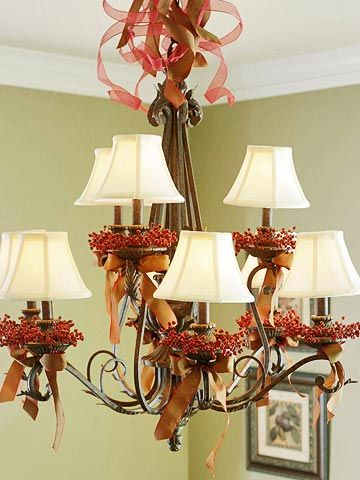 Give a dining room chandelier a Thanksgiving makeover with red berry candle rings and copper satin bows. Sheer and satin ribbon curl into a froth of holiday cheer above the decorated arms. Replace the copper ribbon with ivory for Christmas.