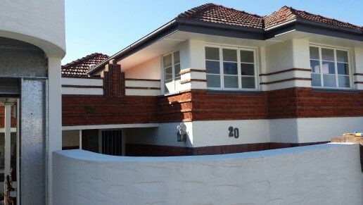 Love the white paint contrasting against two types if red brick in this split-level art deco home, in Red Hill, Brisbane, Australia.
