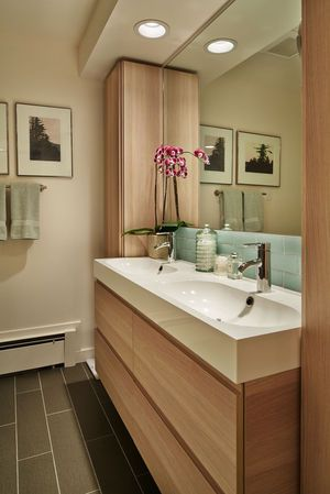 """The bathroom was updated with American Olean plank tiles in """"Sauge"""" on the floor, and a backsplash of recycled glass tile from Bedrock Industries."""