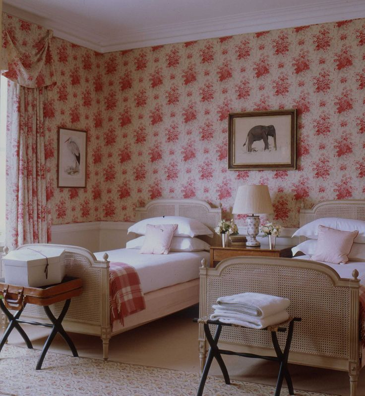 Red, white & beige bedroom with floral wallpaper and caned twin beds with plaid blankets - Todhunter Earle