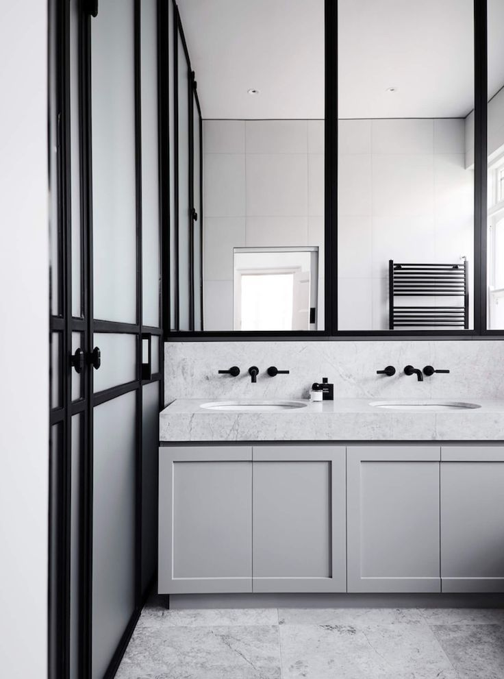Edwardian Elegance: The studio's passion for creative yet luxurious finishes can be seen in the black steel window frames and doors of the bathroom. Characterised by the black steel framing and grey cabinetry and stone, the bathrooms also feature Buster + Punch handles and custom light fittings, reflecting the owner's desire for a contemporary finish. |  Mim Design